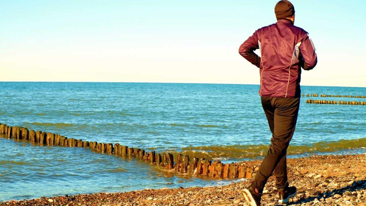 высокий мужчина бежит вдоль пляжа