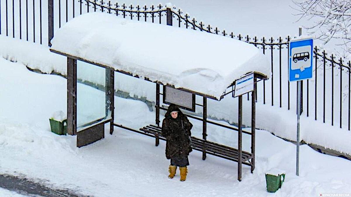Бабушка стоит на остановке зимой