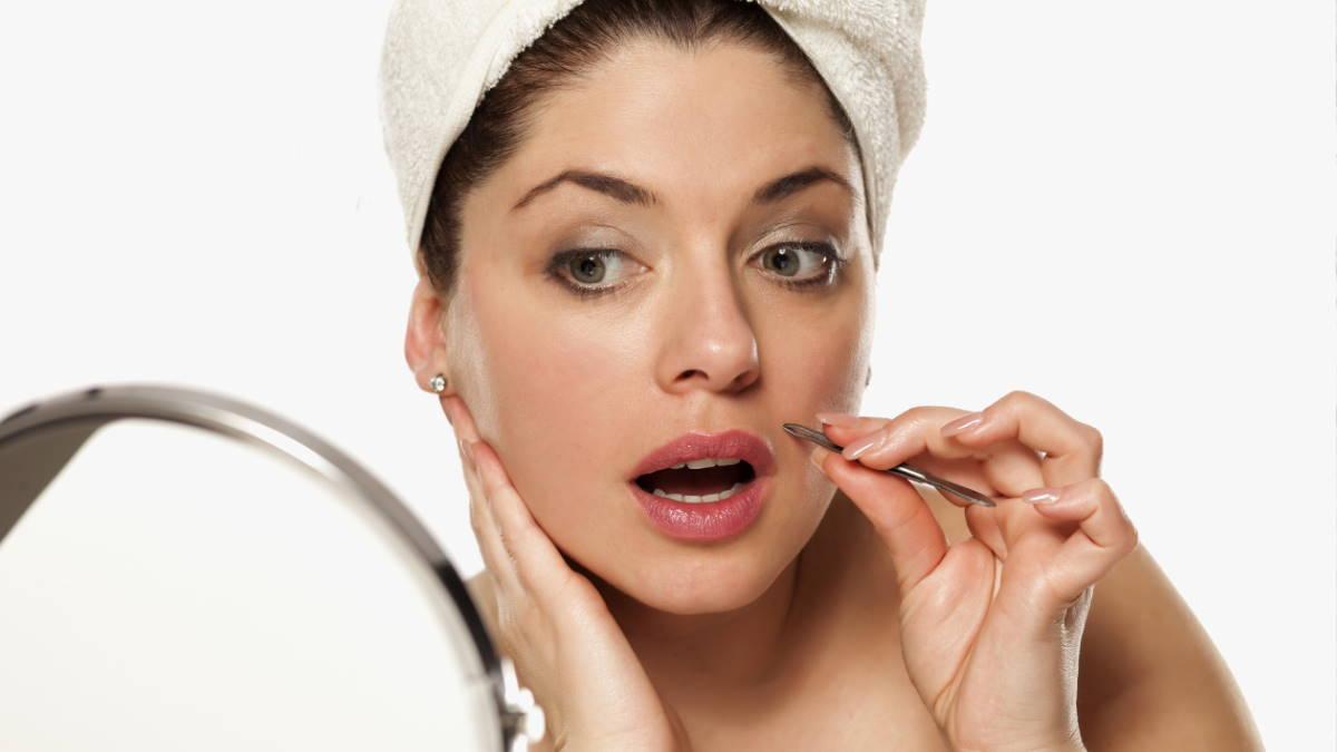 Женщина выщипывает волосы на лице