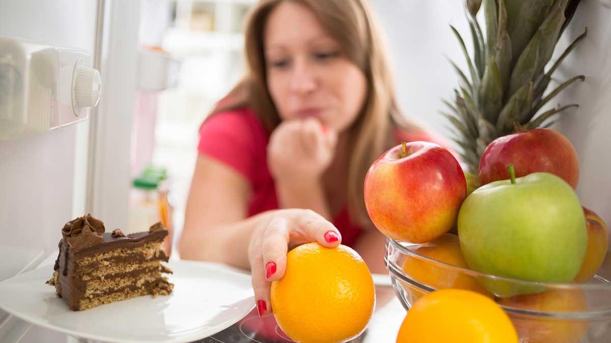 Женщина сомневается, есть ли кусок шоколадного торта или апельсина