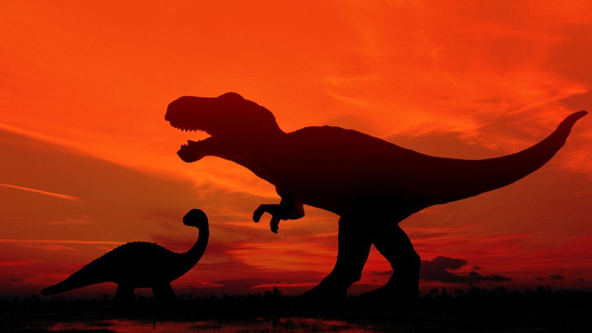 динозавр силуэт хищный на красном фоне
