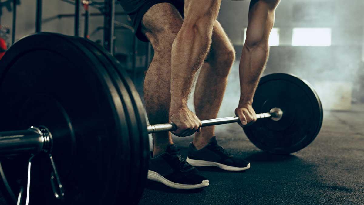 мужчина поднимает штангу спортзал