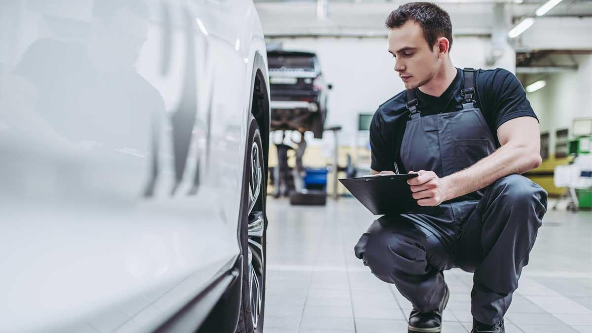 мужчина проверяет тормозные колодки автомобиль