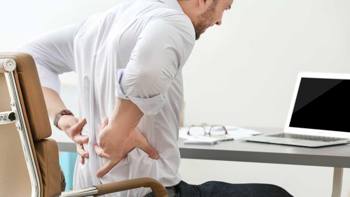 мужчина сидит работает боль в спине