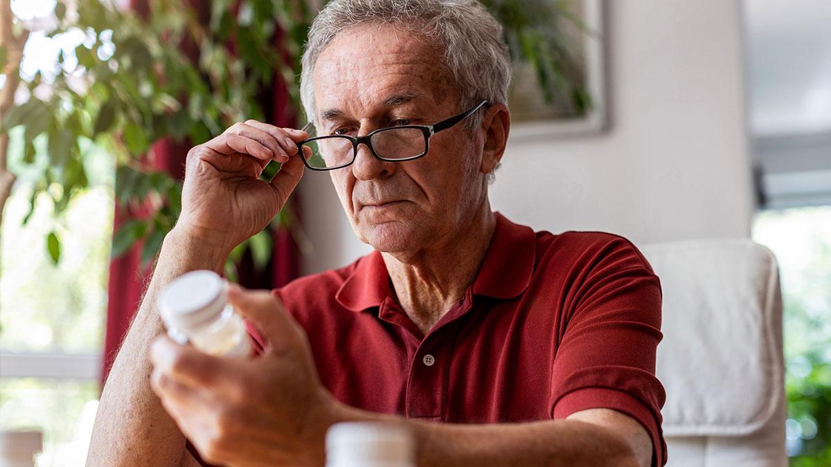 пожилой мужчина смотрит на упаковку витаминов лекарств