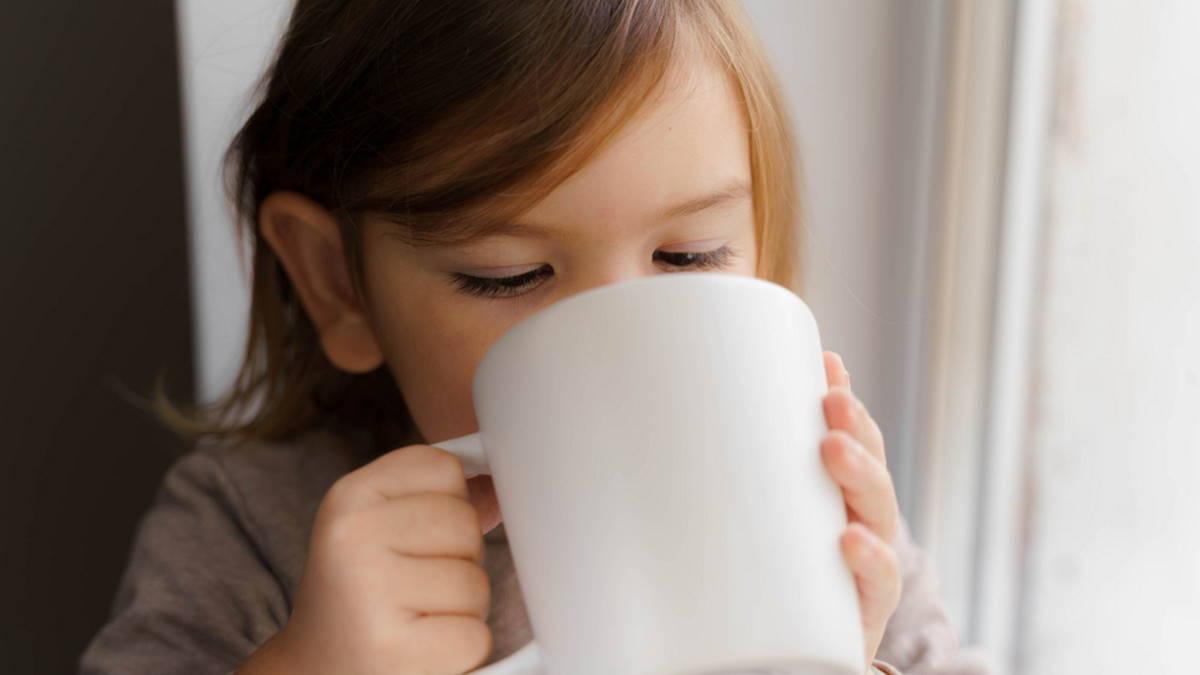 Ребёнок пьёт напиток из кружки