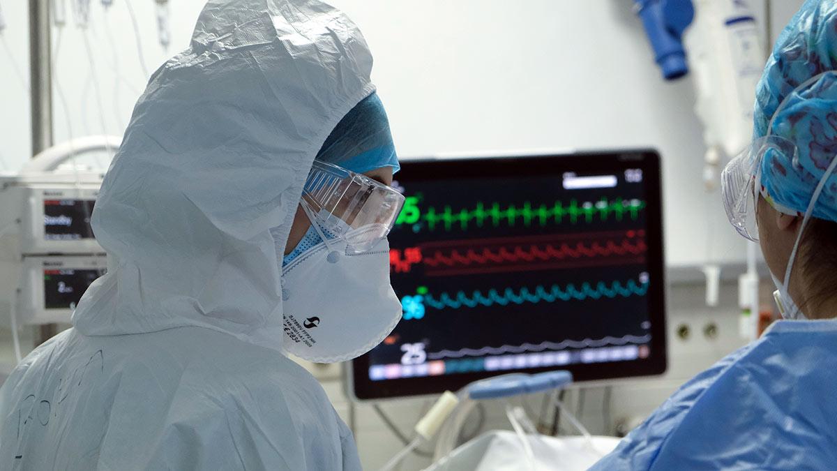 врачи в защитных костюмах коронавирус сердечный ритм