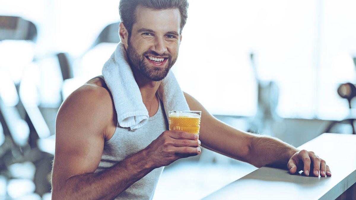мужчина пьет сок во время тренировки