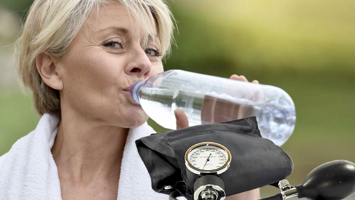 тонометр и женщина пьет воду