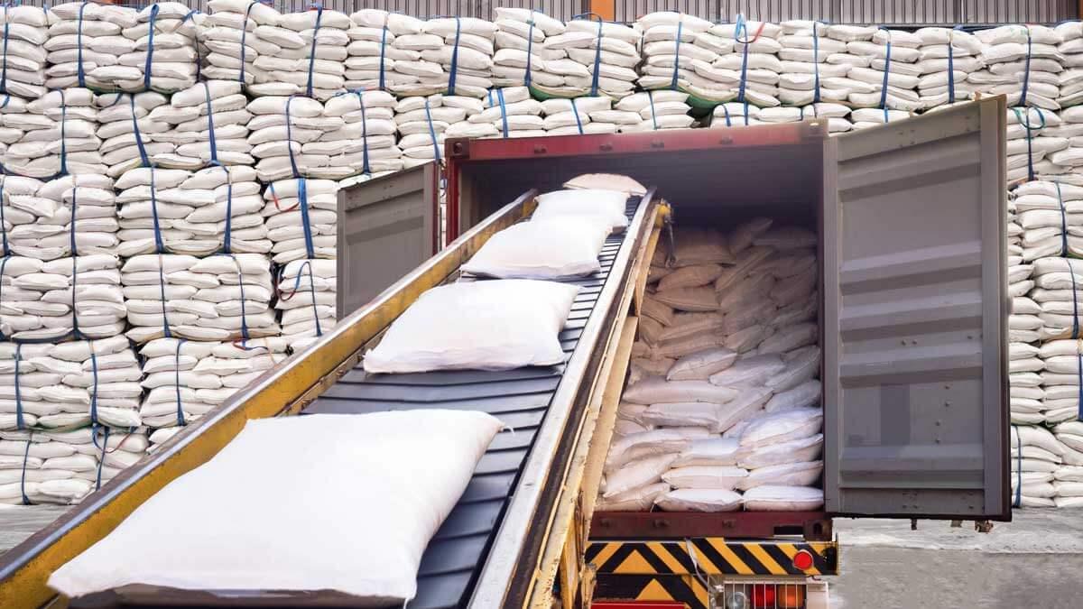Белые мешки сахара со склада заполняются в контейнере