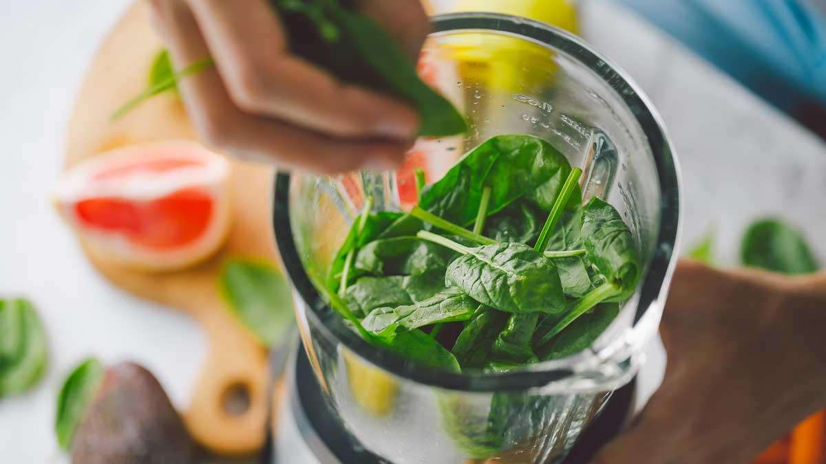 Человек приготовление смузи со свежими фруктами и зеленым шпинатом