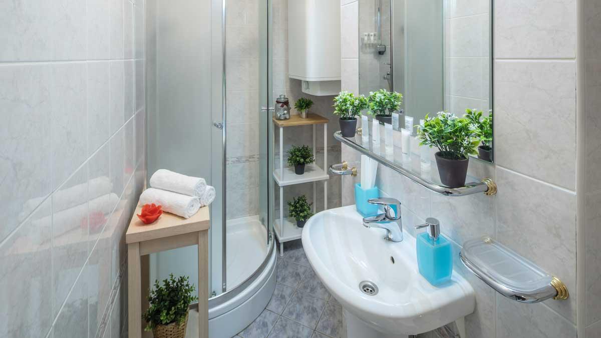 Маленькая ванная комната. Белая раковина. Душевая кабина. Декоративные цветы. Полотенца и зеркала.