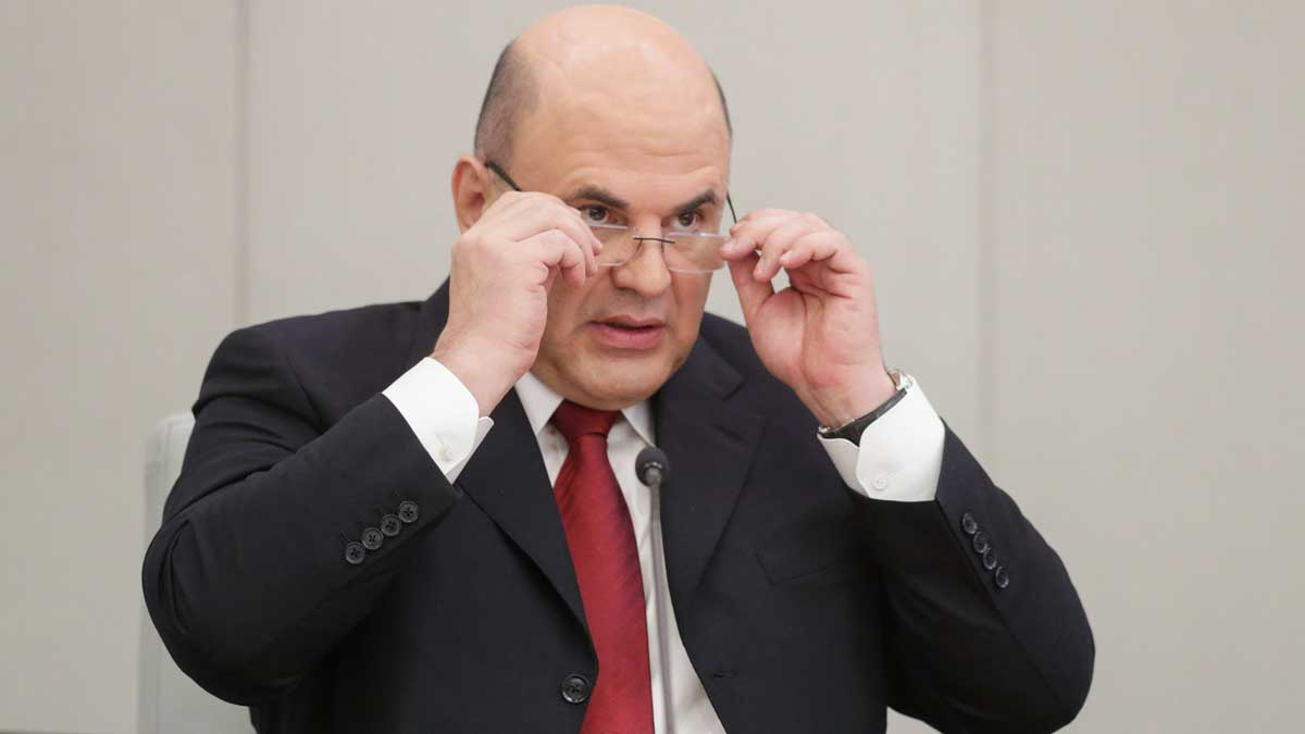 Михаил Мишустин держит руками очки