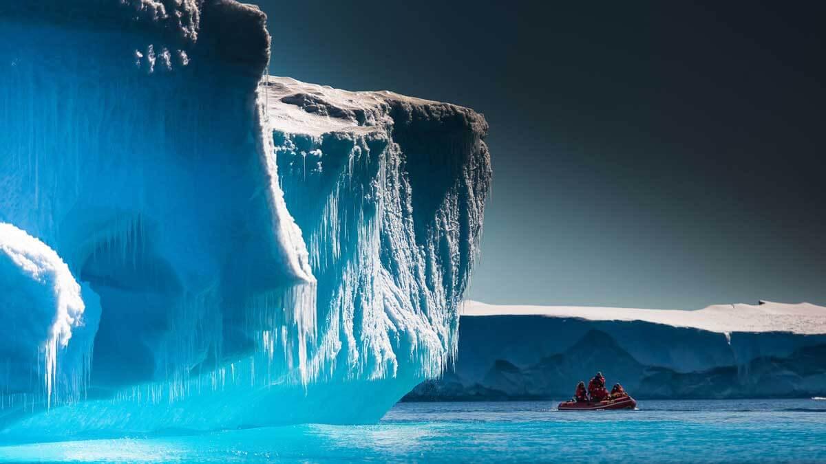 Ученые исследуйте антарктические Айсберги на лодке