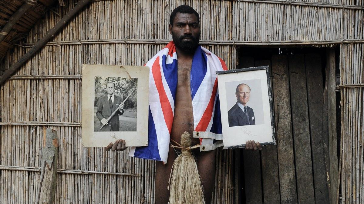 Сын вождя племени на острове Танна в Вануату держит официальные портреты принца Филиппа