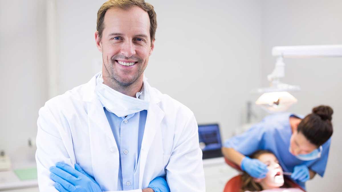мужчина в халате улыбается стоматолог дантист