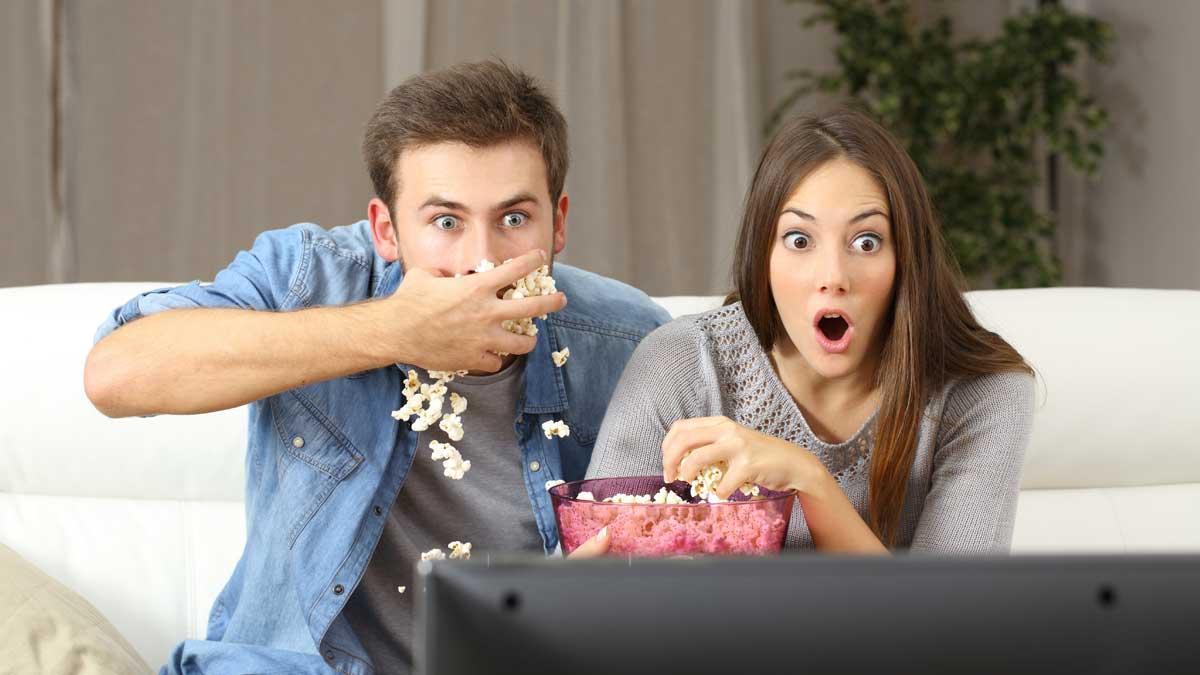 парень и девушка смотрят телевизо едят попкорн шок