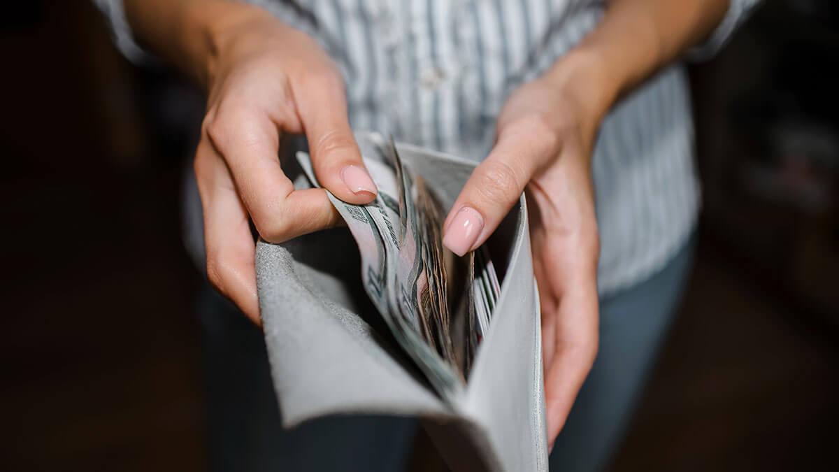 женщина держит в руках кошелек с деньгами рубли