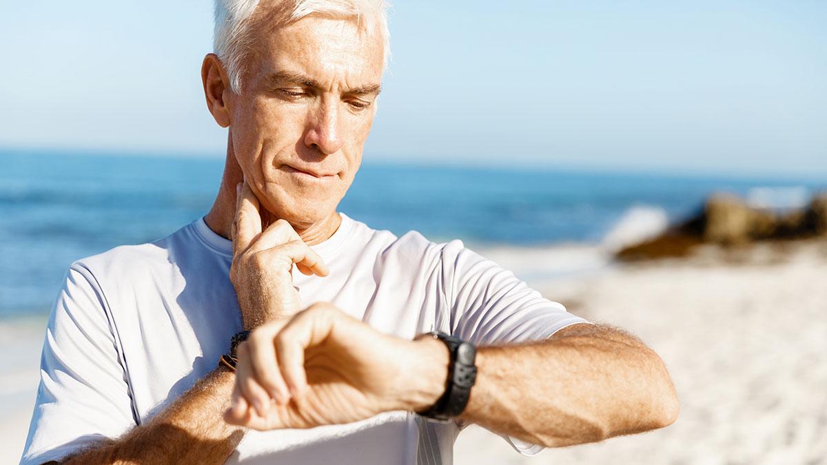 мужчина измеряет пульс смотрит на часы