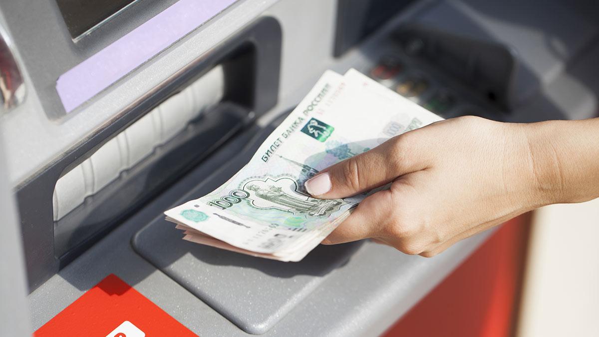 женщина снимает деньги в банкомате зарплата доходы