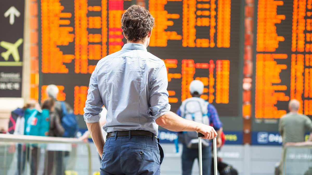 Мужчина в аэропорту ждет рейс