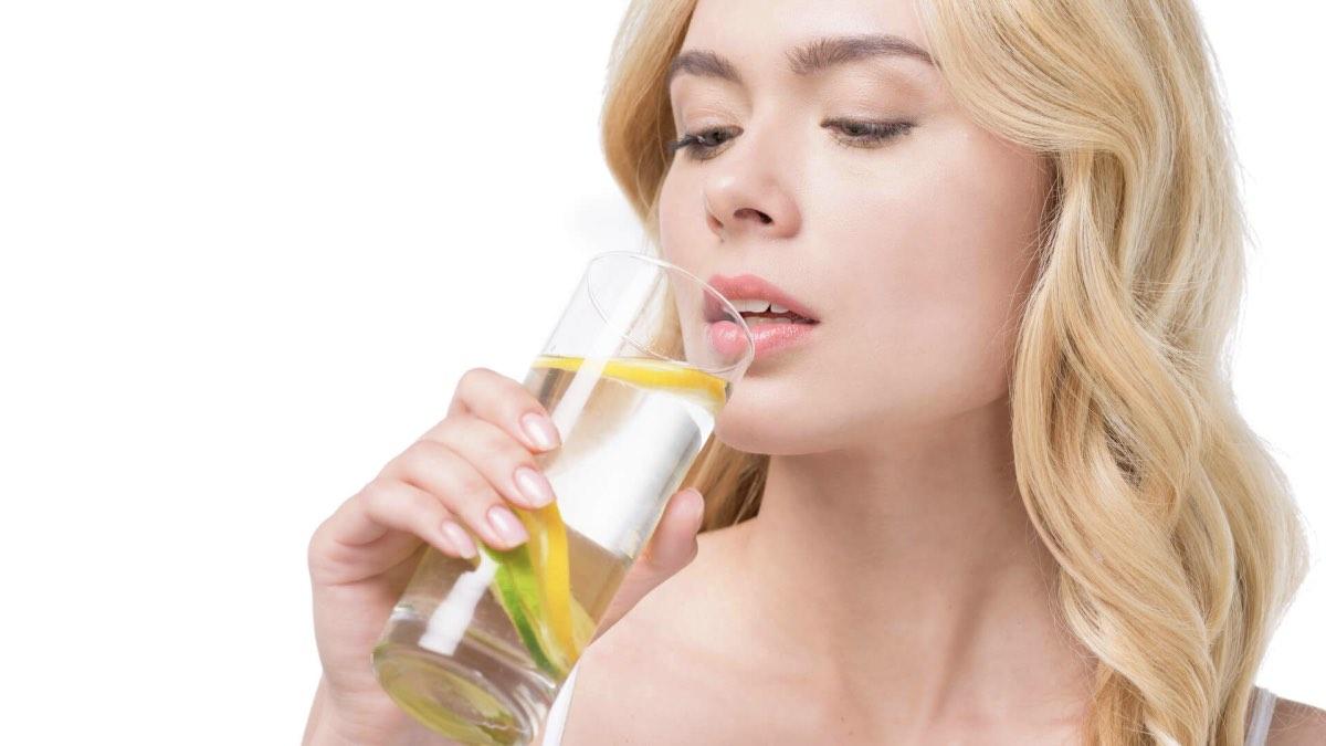 женщина пьет лимонную воду