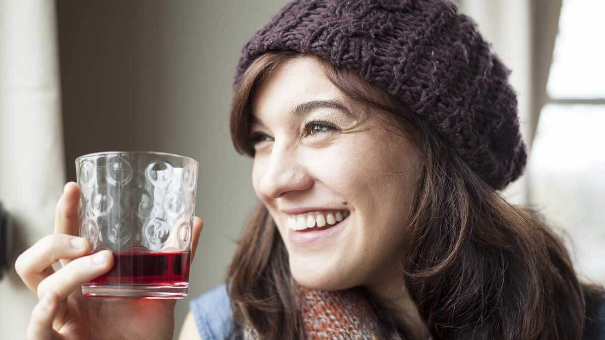 женщина улыбается и пьет сок
