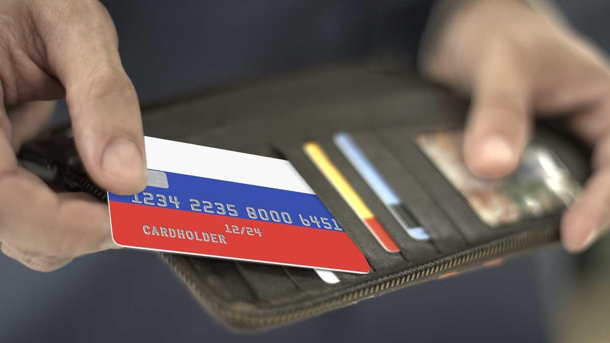 Мужчина достает из бумажника кредитную карту с флагом России