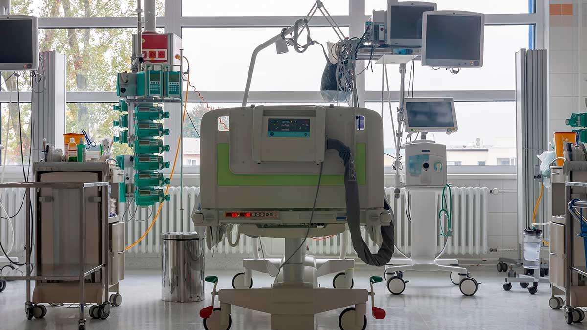 Отделение интенсивной терапии в больнице, кровать с мониторами, аппарат искусственной вентиляции легких