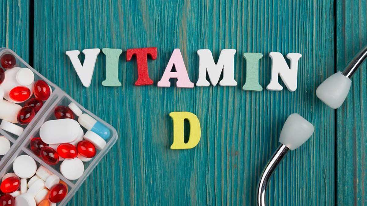 Текст Витамин D из цветных деревянных букв, стетоскопа и таблеток на синем деревянном фоне