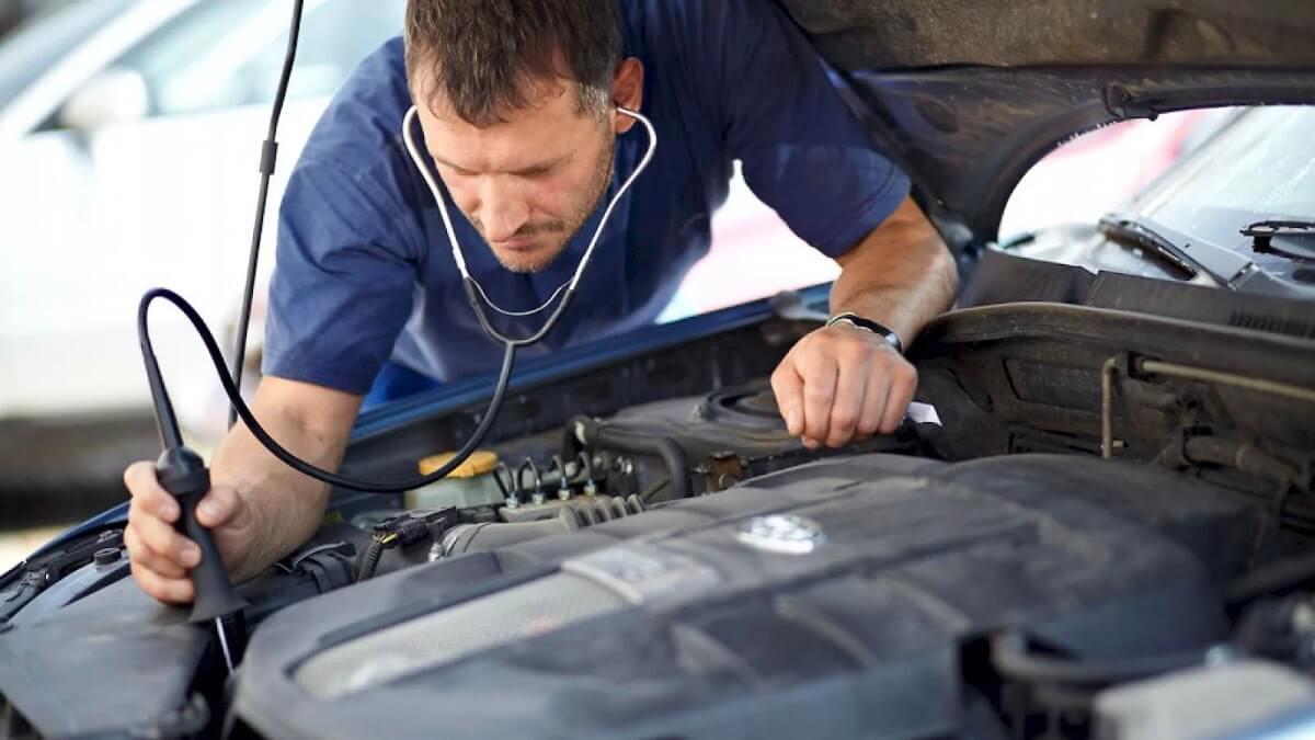 автомеханик слушает двигатель