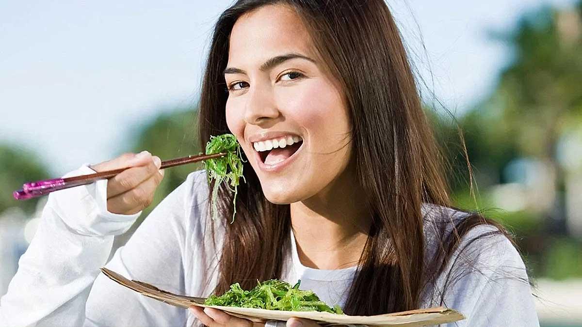 девушка ест морские водоросли и улыбается