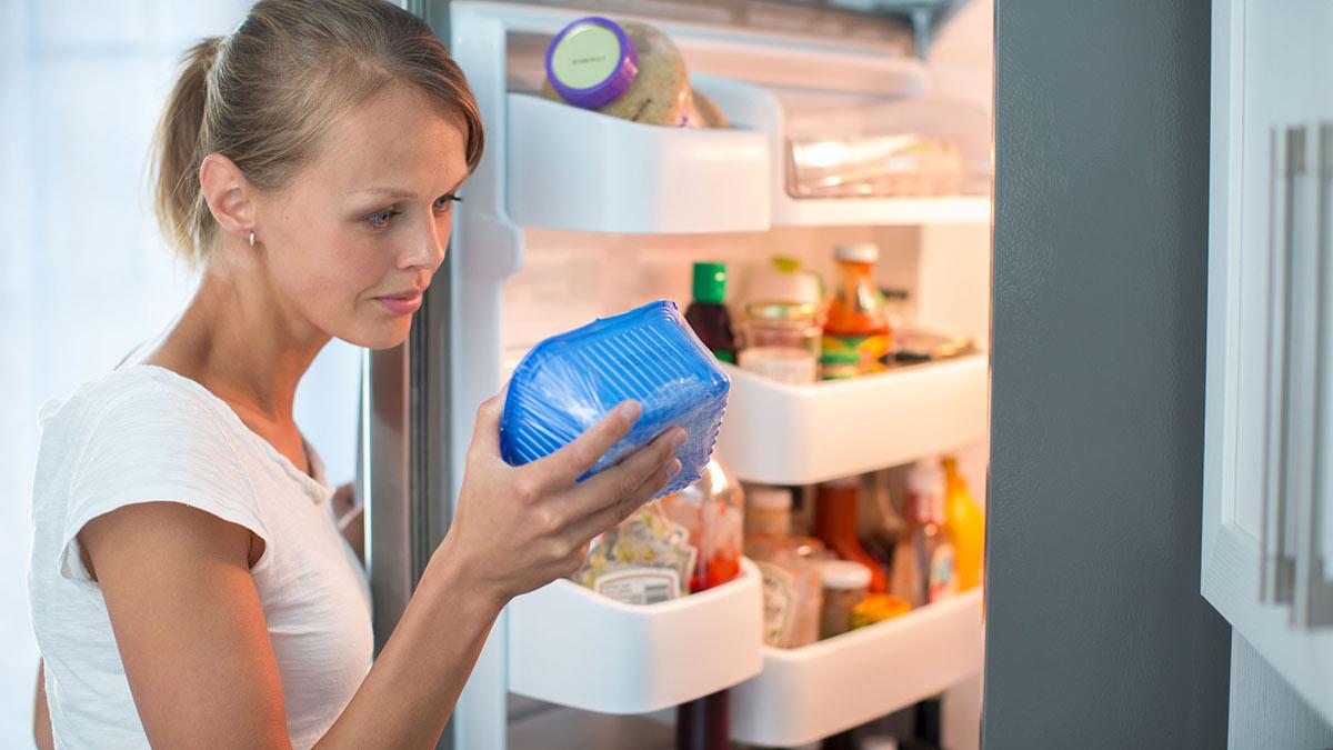 девушка у холодильника выбирает продукты срок годности