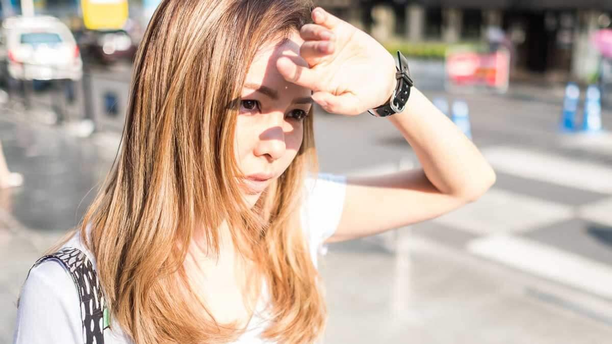 девушка закрывает лицо рукой солнце