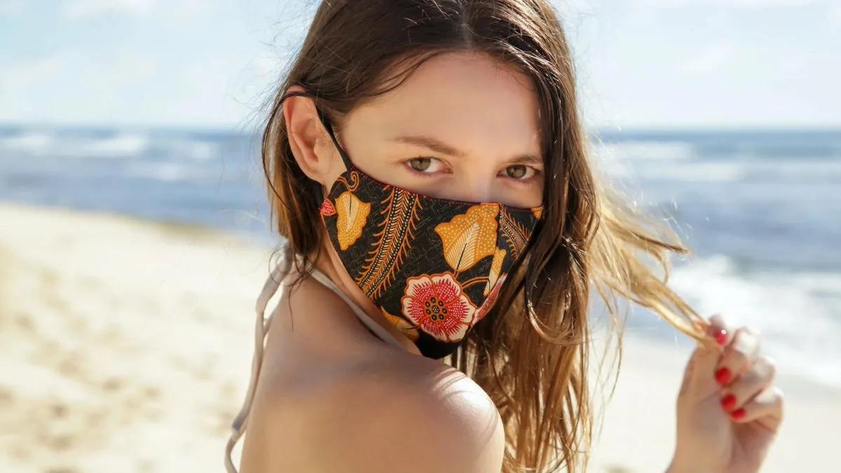 девушка в защитной маске на пляже