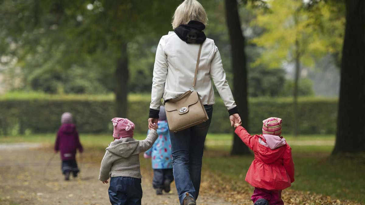 мама гуляет с детьми в парке два