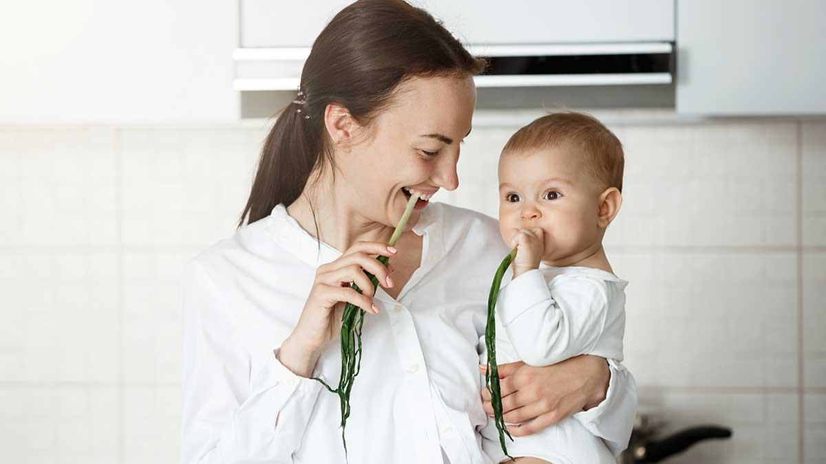 мама с ребенком едят зеленый лук