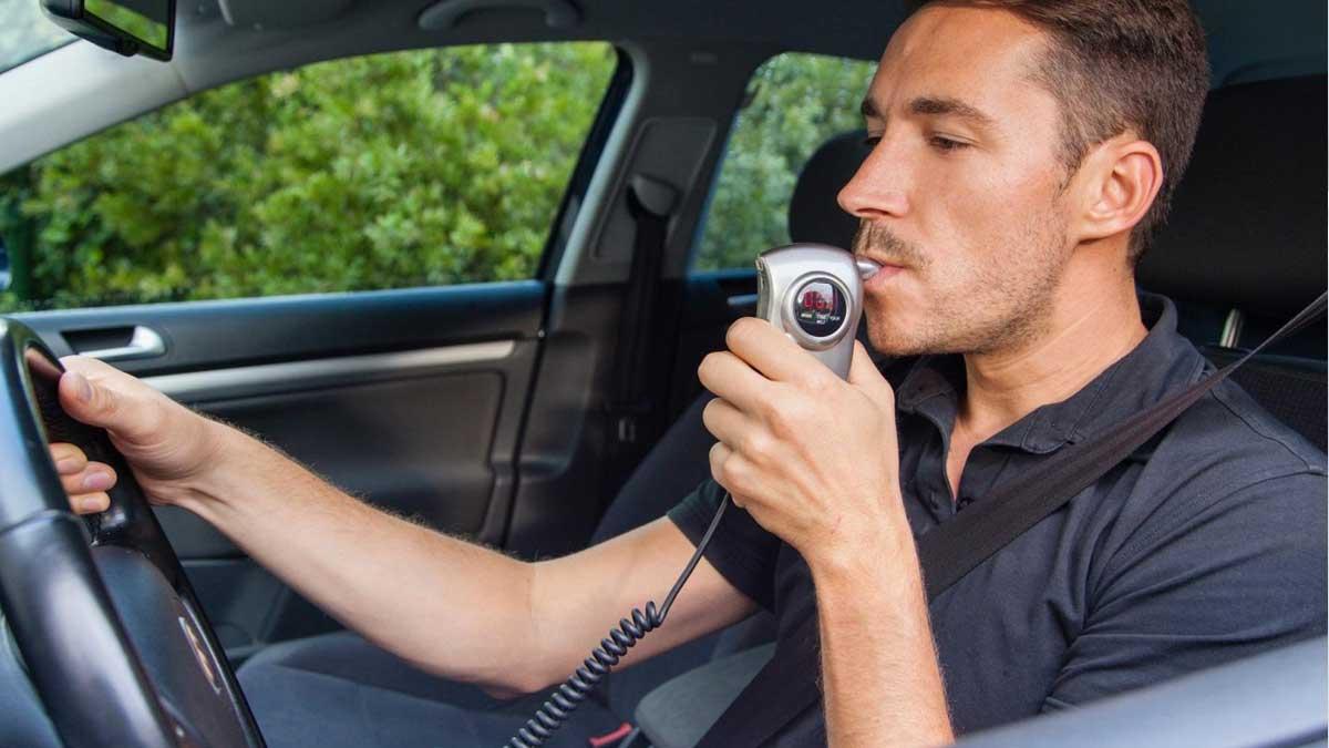 мужчина дует алкозамок автомобиль