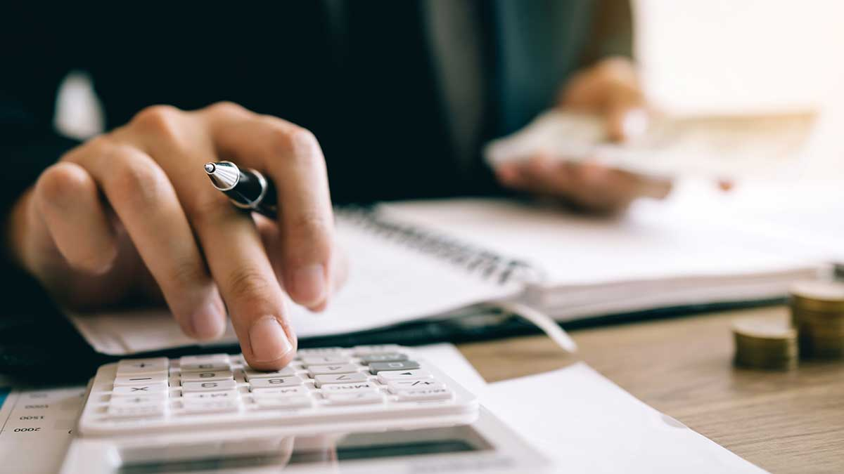 мужчина рассчитывает на калькуляторе инвестиционные затраты и держит в руках денежные купюры