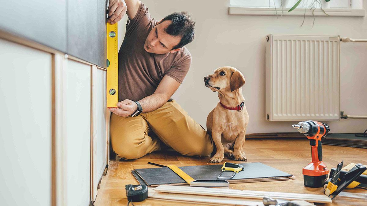 мужчина делает ремонт в квартире