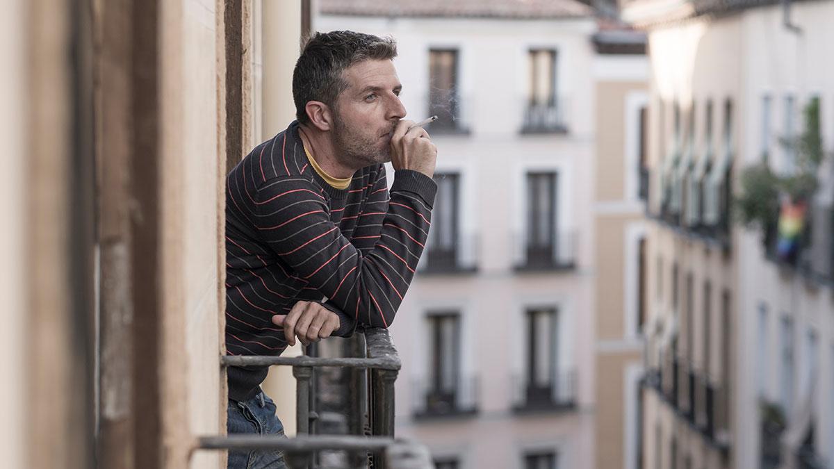 мужчина курит сигарету на балконе