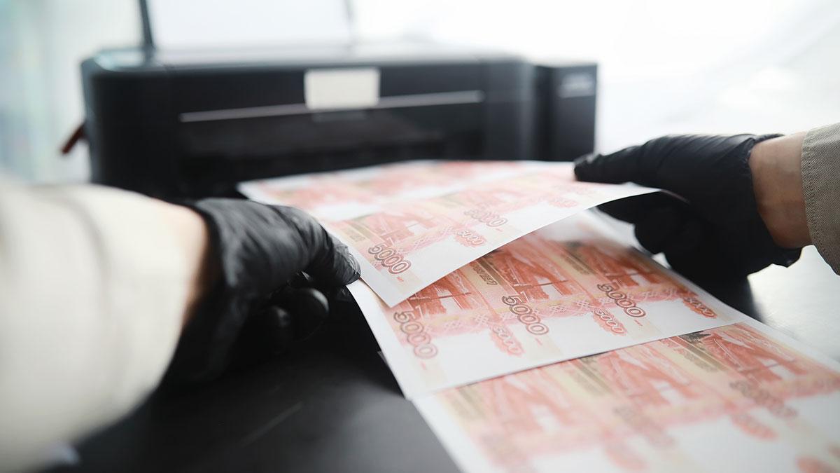 мошенник печатает фальшивые купюры