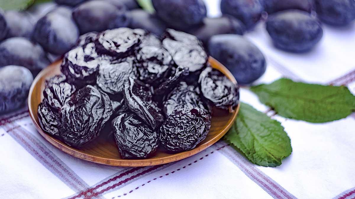 Сушеный чернослив в блюдо на скатерти на фоне свежей сливы