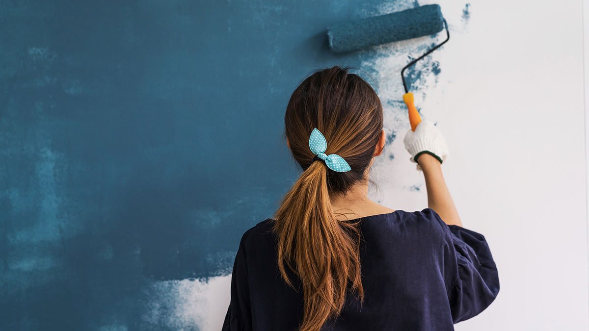 женщина красит валиком стены в синий цвет