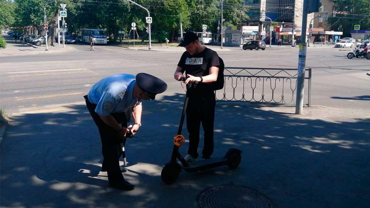 Полицейский осматривает самокат