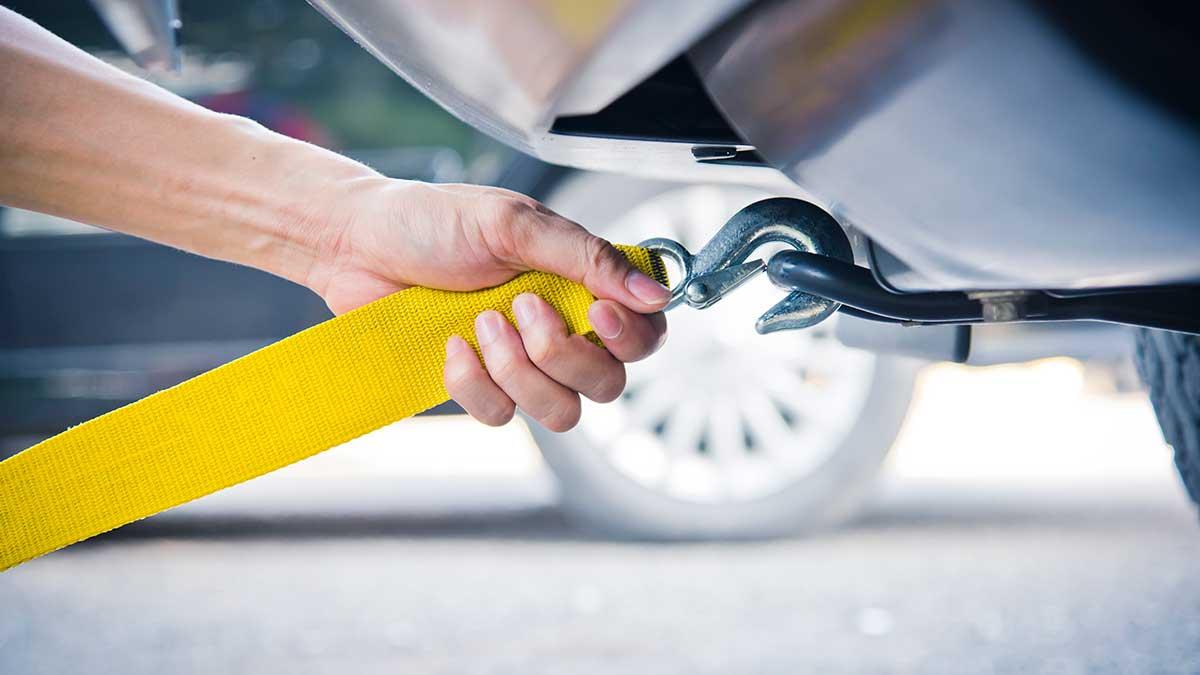 Ручной держит желтый автомобиль буксировки ремень с автомобилем