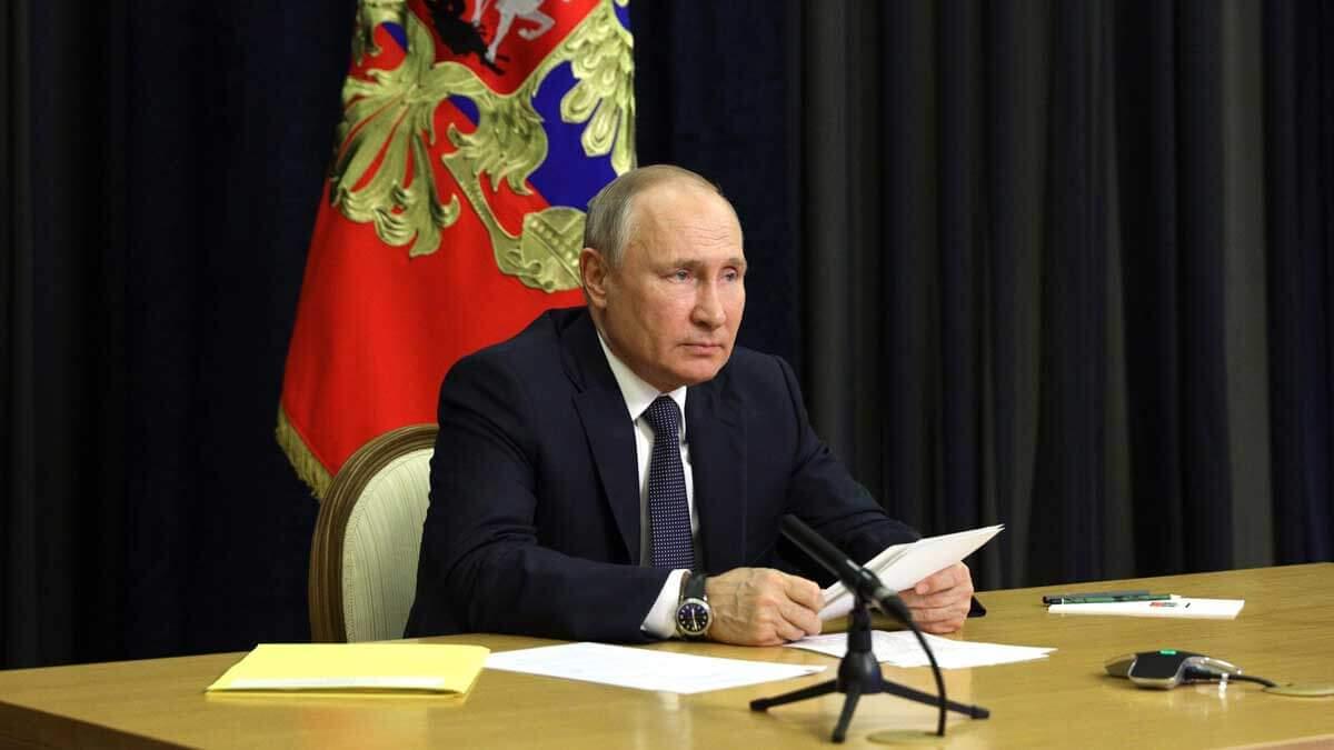 Владимир Путин сидит за столом часы бумага микрофон
