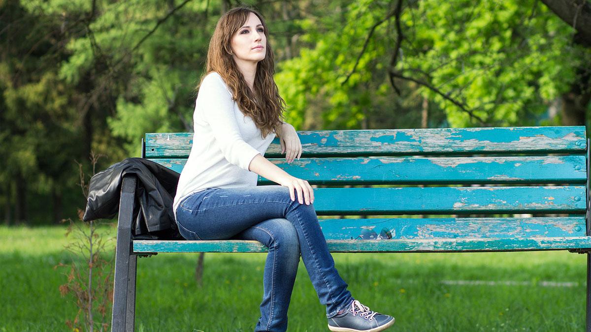 девушка сидит на скамейке в парке лето