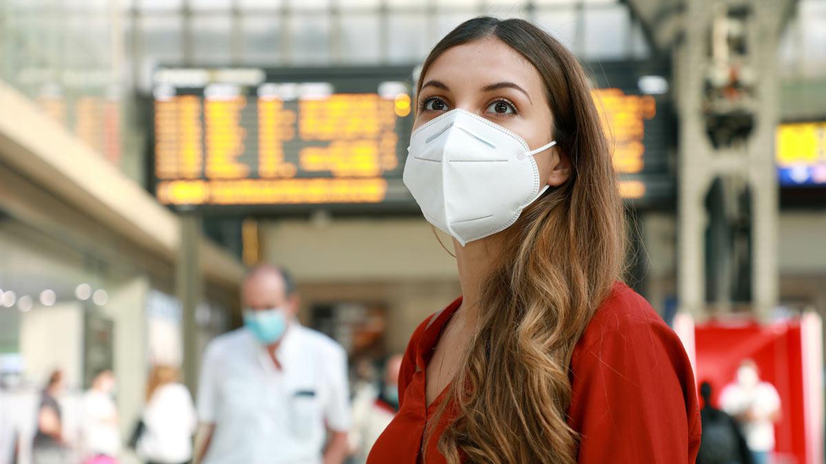 девушка в маске в аэропорту в красном