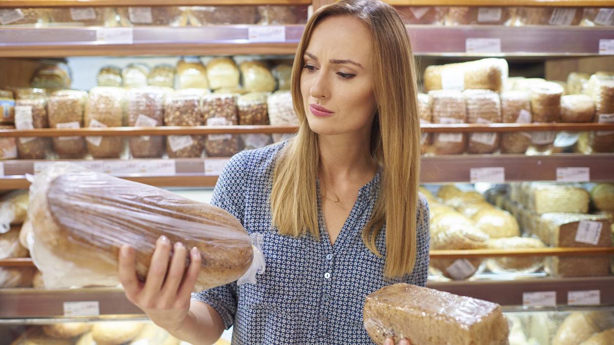 девушка выбирает хлеб в магазине